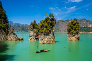 Aerial drone view of longtail boats around spectacular limestone fingers and karsts on a huge lake surrounded by jungle